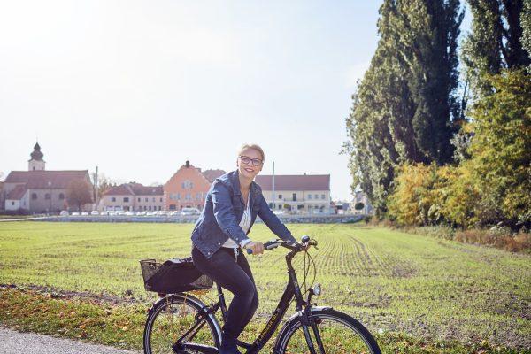 Bürgermeisterin Marion Török fährt mit dem Rad an der Donaulände. Im Hintergrund ist Zwentendorf zu sehen, mit dem Rathaus und der Pfarrkirche.