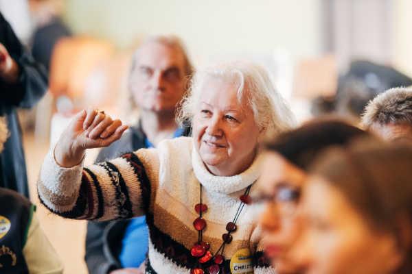 Ältere Frau, die sich bei einer Diskussion zu Wort meldet
