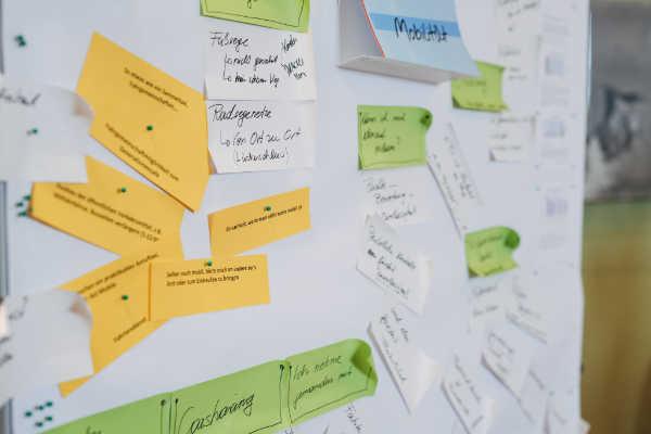 Pinwand mit vielen Zetteln, auf denen Ideen notiert sind