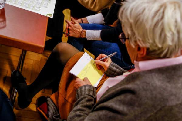 Ältere Frau notiert eine Idee auf einen Zettel für die Pinnwand