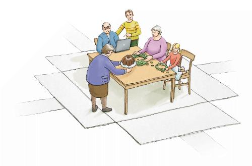 Der alte Mann sitzt mit jüngeren Menschen gemeinsam an einem Tisch, es gibt Kuchen und der alte Mann sitzt dabei vor einem Laptop