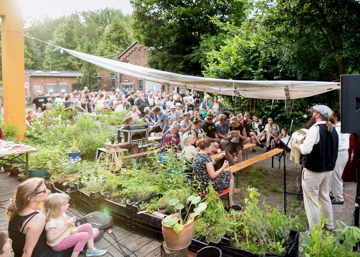 Musiker und Publikum bei einem Open Air in einem Fabrikhof