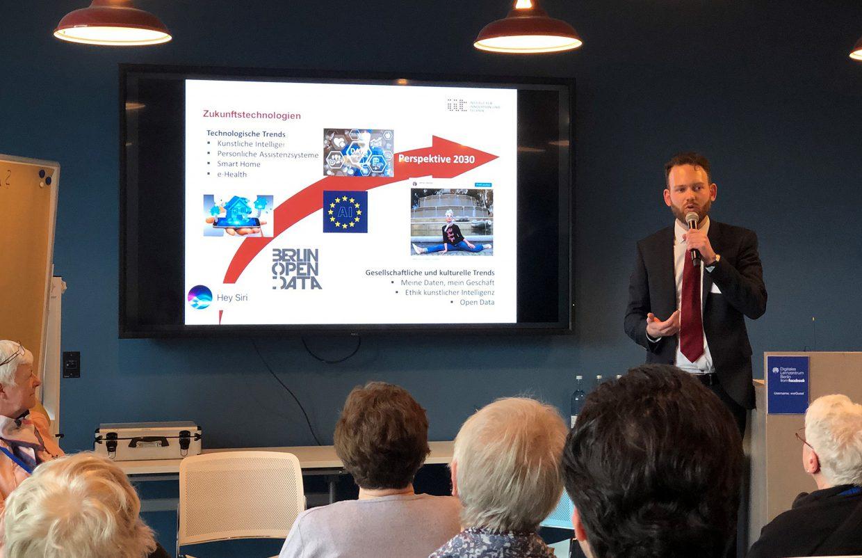 Vortragender vor einem großen Bildschirm zum Thema Zukunftstechnologien
