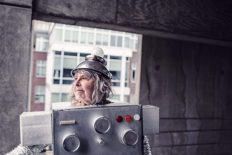 Ältere Frau in kuriosem, offenbar selbst gebastletem Roboterkostüm