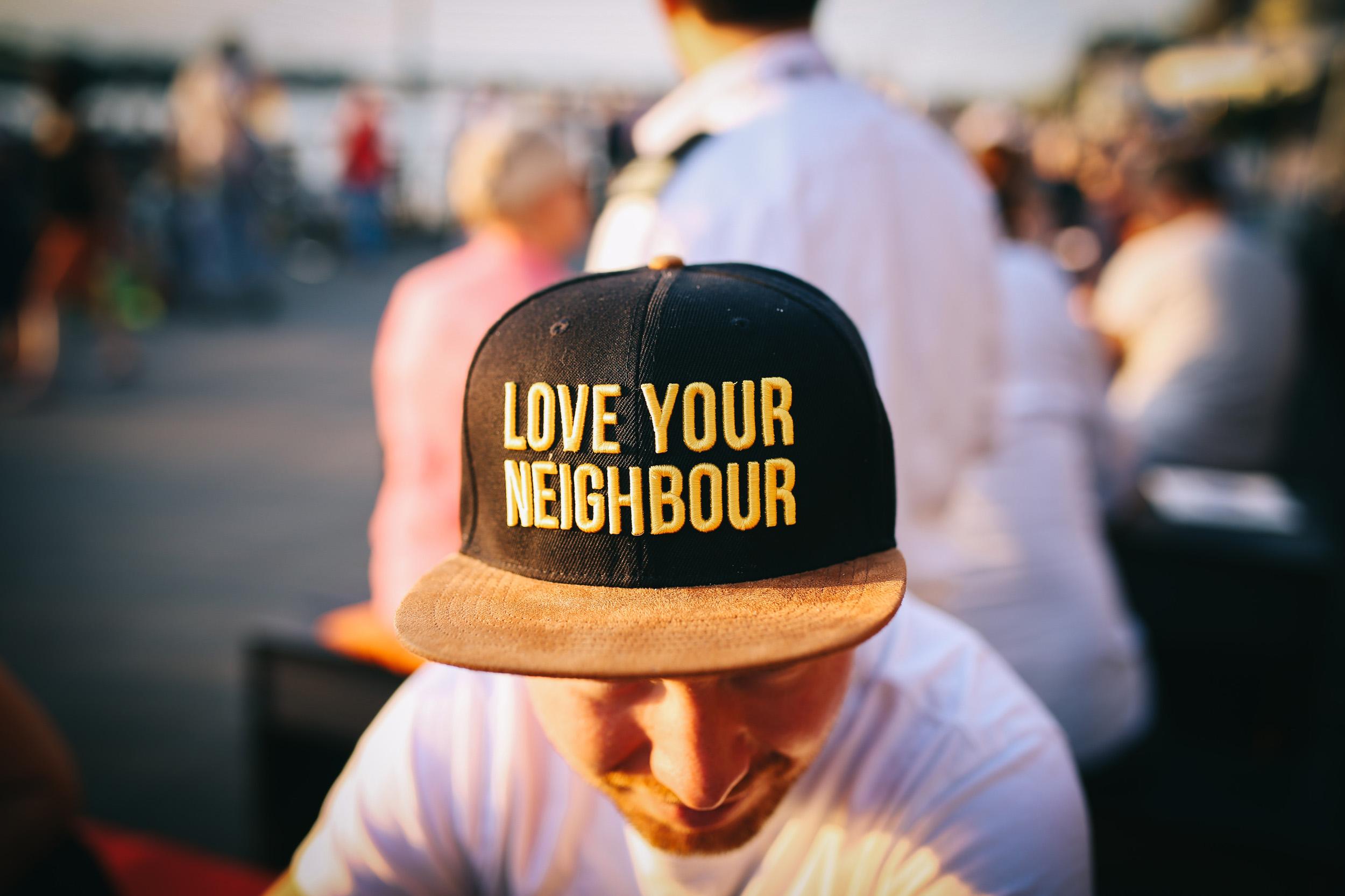 """Kappe auf dem Kopf eines jungen Mannes, auf der """"Love Your Neighbor"""" steht"""
